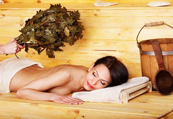 Девушку массируют веником в бане