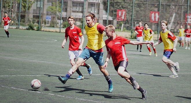 Мужчины играют футбол на домашнем поле