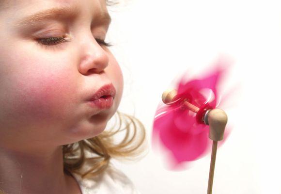 Девочка дует на пропеллер