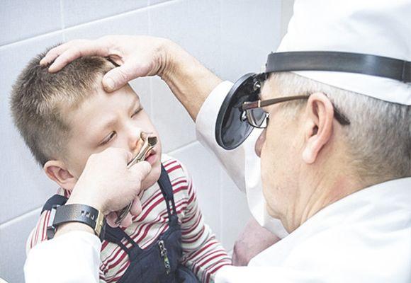 Врач осматривает носовую полость ребенка